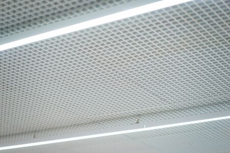 Lighting and ceiling finishes in of the modern ceilings and interior in the office. Lighting devices. Silver metal grill on the ceiling. Reklamní fotografie
