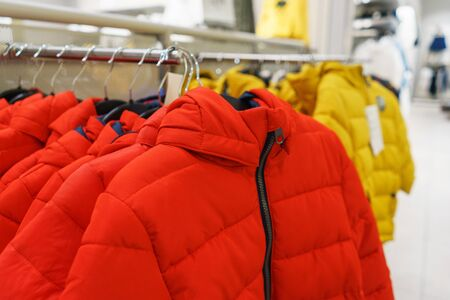 Modern fashion store. Buyers choose clothes. Autumn outerwear on hangers in a fashionable clothing store for children and adults.. Sale and shopping in stores. Soft focus.