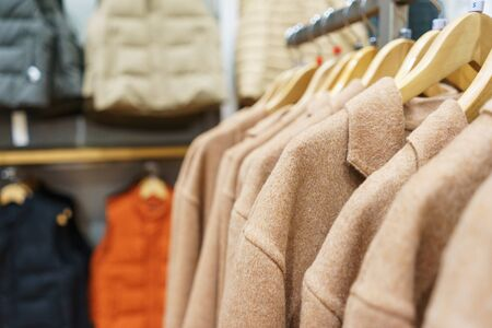 Modern fashion store. Buyers choose clothes. Fashionable mens and womens clothes on hangers in a clothing store. Sale and shopping in stores. Soft focus. Stock fotó