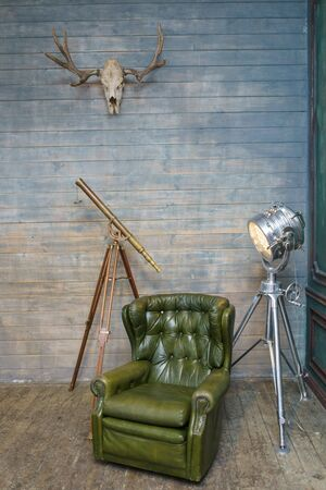 Vintage furniture and decor details in a rustic room. Stylish study with antique furniture. Leather armchair, a telescope and a stylish lamp a metal floor lamp against a wall of wooden boards.