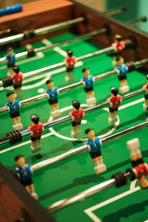 Foosball, miniature plastic players of blue and red teams against each other. Entertainment and games. Competition and challenge. Results and goal, concept. Vintage toning. Stock Photo