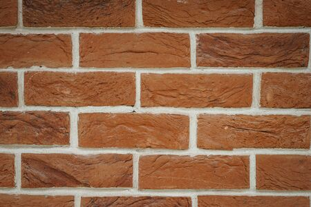Red brick wall closeup. Abstract background. Brickwork and glue, gray seams between bricks. Style and details of interior design. Soft focus and bokeh. Stock Photo