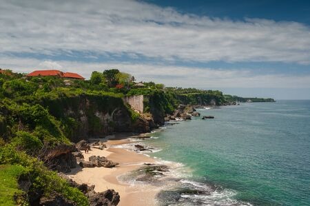 Tropical seascape. Ocean, waves and blue sky. Tropics. Beach and beautiful views of the cliffs, splashing waves and nature. Bali Island.