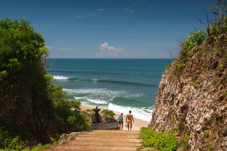 Tropical seascape. Ocean, waves and blue sky. Tropics. Beach and beautiful views of the cliffs, splashing waves and nature. Stone stairs in the rocks on the way to Balangan beach. Bali Island.