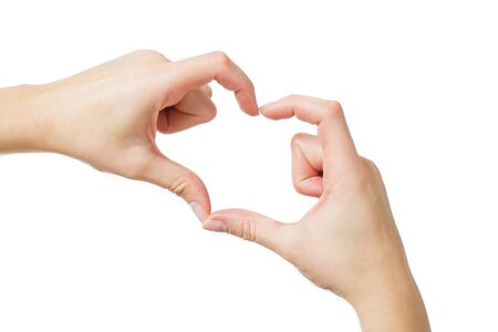 Top view: female hand with clean healthy skin on a white isolated background showing gestures with the fingers. Soft focus, shallow depth of field. Gesture - heart, love. Stock Photo