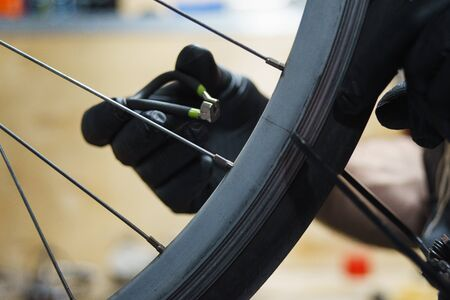 Workshop on maintenance and repair of bicycles. Details, close-ups, bicycle maintenance process. Handicraft workshop. Tools, workbench and bike rack. Service man adjusts and balances the wheel.