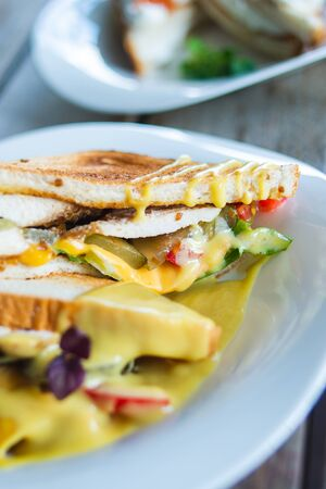 Classic breakfast, hot sandwiches with cheese, vegetables and chicken on a wooden table. Hand-made, rustic breakfast, toast with turkey and vegetables. Soft focus.