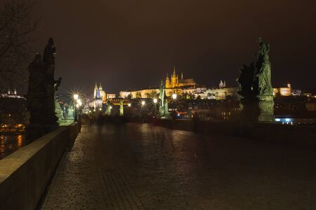 Charles Bridge tourist attraction in Prague, capital of Czech Republic. Long exposure, blurry people at night while walking around the city. Travel old European city. Autumn season. Night photography