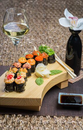 Set of several different rolls on a wooden stand on a table in a Japanese restaurant. Japanese traditional sushi and rolls. Sea products. Beautiful table setting with flowers and wine in glasses. 写真素材