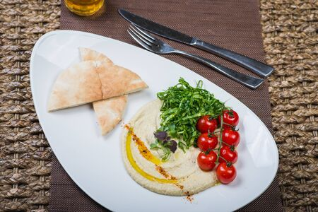Traditional appetizer hummus with bread cakes, pita, on a plate with vegetables and sauce. Creative serving of classic snacks on a wooden table in a restaurant or cafe. Soft focus.