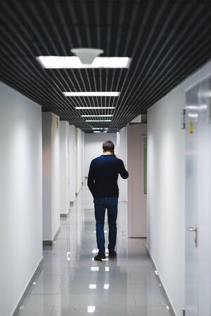 Company employee is talking on a cell phone in the corridor. Interior internal corridor industrial premises, laboratories or institutions with light walls, black ceiling and shiny floor. Soft focus.