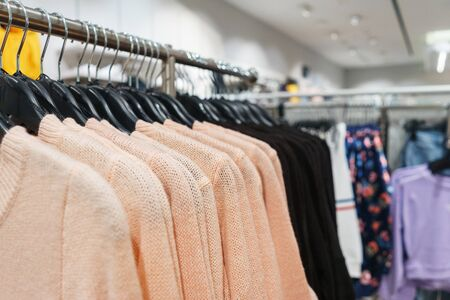 Modern fashion store. Buyers choose clothes. Shirts, hoodies, blouses and half-sweaters, a sweater on a hanger in a clothing store close-up. Sale and shopping in stores. Soft focus.