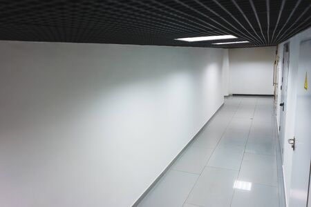 Interior internal corridor of modern office, industrial premises, laboratories or institutions. Corridor with light walls, black ceiling and shiny floor. Soft focus. 写真素材