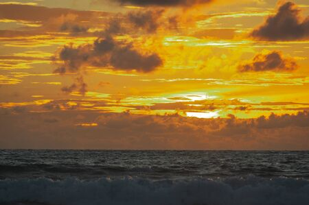 Magical dramatic sunset on a tropical beach. Seascape, ocean waves and bright clouds in the sky. Golden hour. Rest seashore, beach vacation. Concept. Clouds in the sky are painted in different colors.