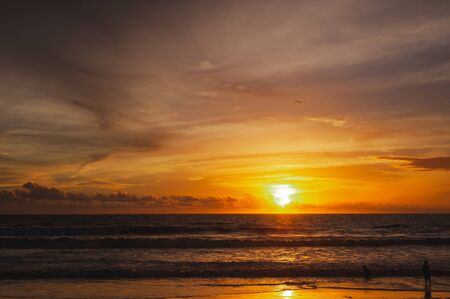 Large bright circle of the sun in the clouds touches the ocean at sunset. Touchdown. Magical dramatic sunset on a tropical beach. Seascape, ocean waves and bright clouds in the sky. Golden hour.
