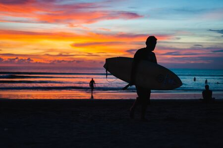 Magical dramatic sunset on tropical beach. Black silhouette of a surfer with a board on background ocean and sky during sunset. Seascape, ocean wave. Soft focus, no noise reduction.