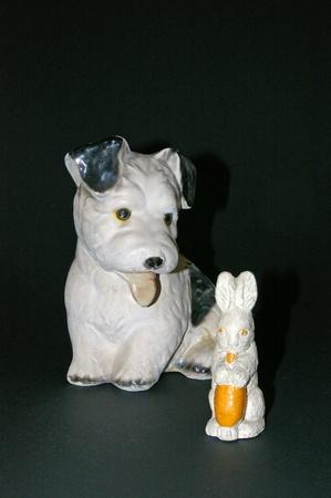 Las pequeñas figuras de tiza de antigüedades de un lindo perro blanco y negro con la lengua fuera y un conejito masticar una zanahoria Foto de archivo - 12451927