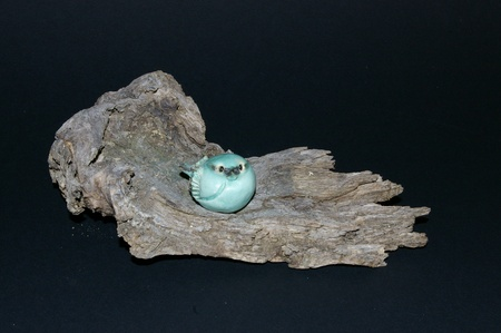Still life of a baby bluebird figurine sitting on a piece of weathered driftwood. Stock Photo