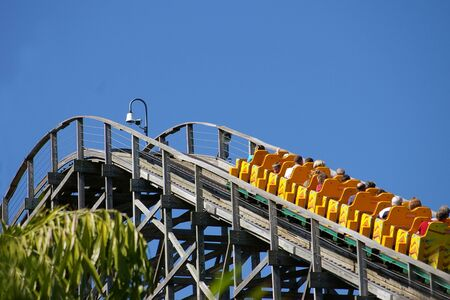 Oblique rear view of a roller coaster full of people mounting a curve in the track photo