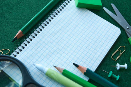 Stationery set on green background. School supplies top view for advertising and promotional items. Back to school concept