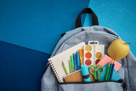 Stationery set with knapsack on blue background. School supplies top view for advertising and promotional items. Back to school concept Reklamní fotografie