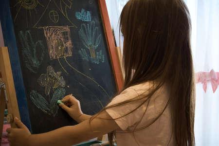 Little girl draws with chalk on the blackboard . The development of creativity. Drawing lesson Reklamní fotografie