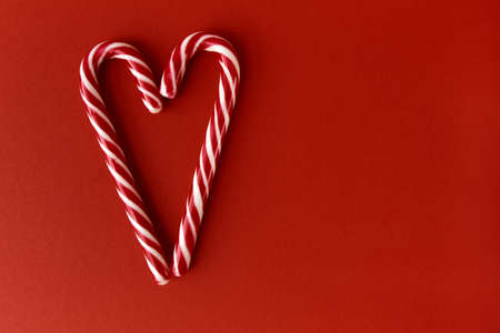 Merry Christmas and Happy New Year greeting card. Xmas holiday red background. Heart made of candy Stock fotó