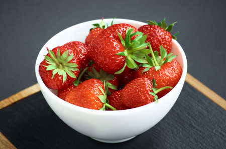 Strawberries on black background. Berries in a plate