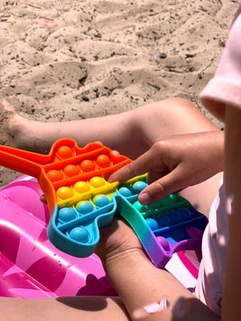 Little girl plays with cotton on the beach. A modern toy for toddlers. Antistress toy