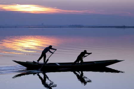 Venice sunset silhouette of sinchronized rowing men Stock Photo