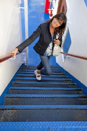 smiling girl climbing the blue stairs of a ferry Stock Photo