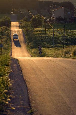 car running on asphalt downhill at sunset dusk Stock Photo