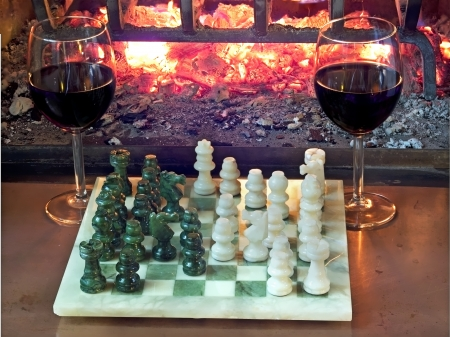 play chess drinking red wine in front of a roaring fireplace Stock Photo