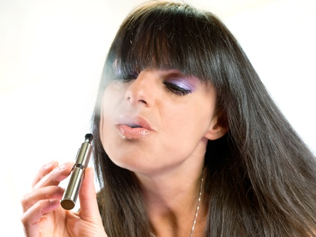 brunette beautiful girl smoking electronic cigarette photo