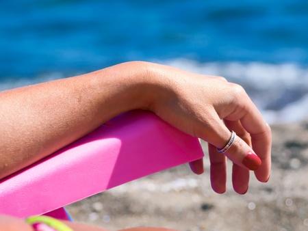 女性は海に面したビーチでデッキチェアで寛ぎます