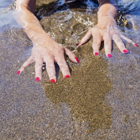 woman hands on the water foreshore,  black sand