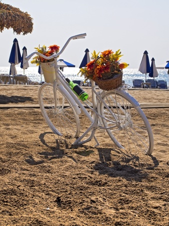 bicycle parked on a beach next to the sea umbrellas photo