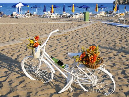 bicycle parked on a beach next to the sea umbrellas