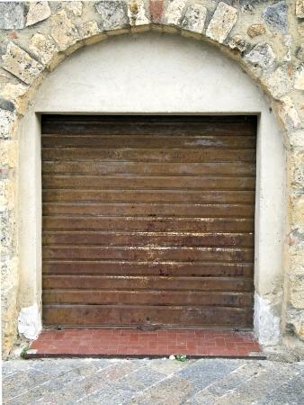portcullis: rusty shop rolling portcullis of stone house is closed
