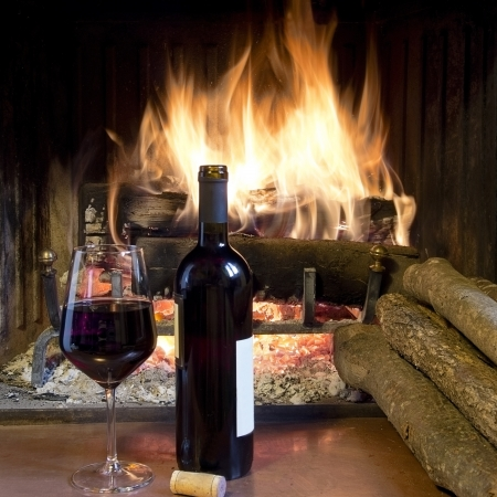 romantic evening with wine: celebrate with a glass of wine, a bottle, in front of a fireplace