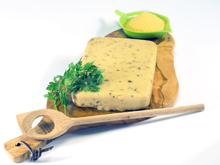hardened polenta on a wooden olive chopping board   Stock Photo