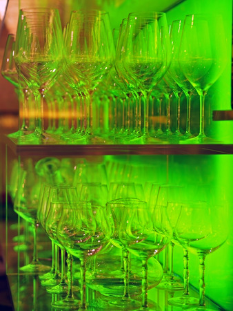 chalices:   crystal glasses  lined up in illuminated glass display  case  Stock Photo