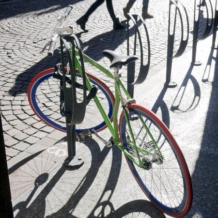 locked colored bike  parked on the sidewalk with shadows