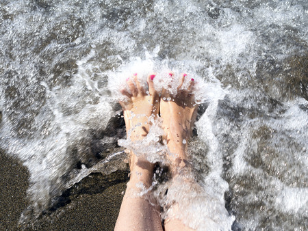 woman feet relaxing on the shore waiting for the wave