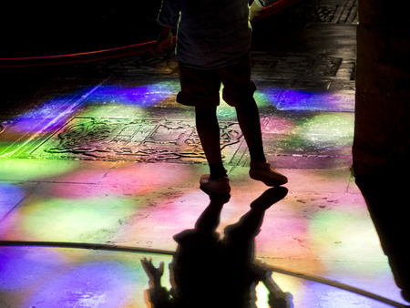 leg Silhouette on a church tumb floor with colored light reflections Stock Photo