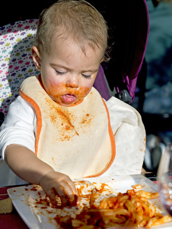 smeared hand: baby girl gets dirty face with tomato eating  pasta with her hands