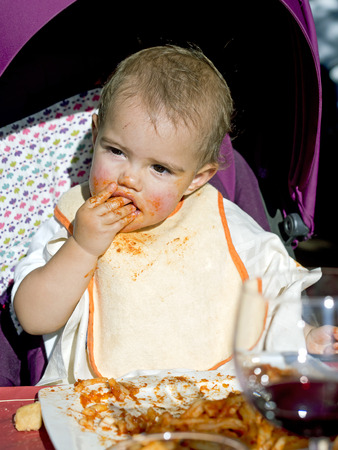 anointed: baby girl gets dirty face with tomato eating  pasta with her hands