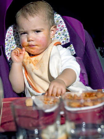 baby girl gets dirty face with tomato eating  pasta with her hands photo