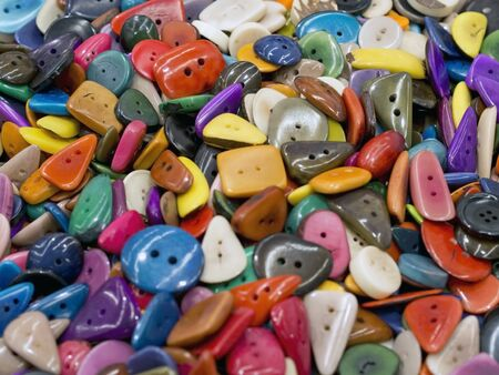 many irregular colored buttons of various shapes  on each other