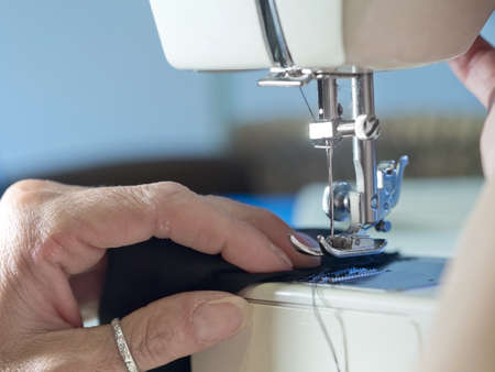 hand of  woman working cloth with  old sewing machine